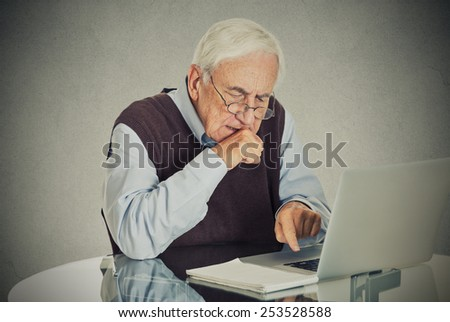 Confused grandfather using a pc - stock photo