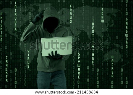 Confused hacker looking at a laptop computer - stock photo