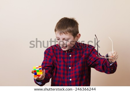 Confused little boy  little boy nerd ,holding a puzzle cube. - stock photo