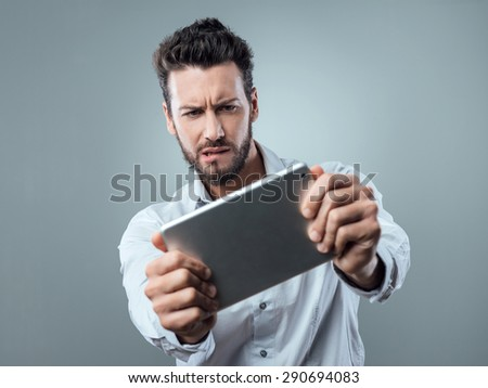 Confused man biting his lip and watching a digital tablet