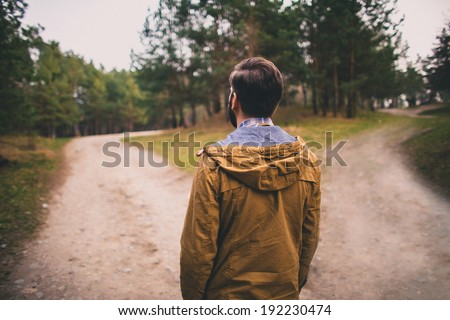 confused man chooses road outdoor  - stock photo