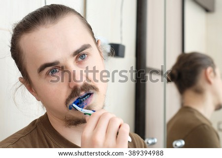 Confused man cleaning his teeth with blue color for April Fools joke - stock photo