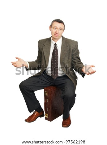 Confused man sits on suitcase