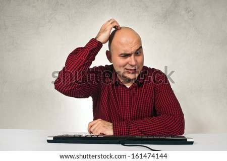 Confused man sitting at office table in front of the computer keyboard. Computer problem.