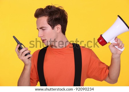 Confused man with a loudspeaker and walky-talky
