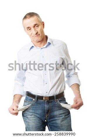 Confused mature man showing his empty pockets.