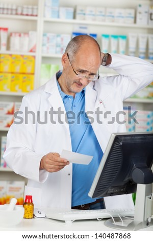 Confused mature pharmacist holding prescription paper at pharmacy counter - stock photo