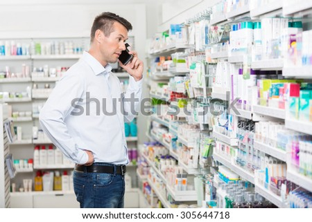 Confused mid adult man using mobile phone while looking at products in pharmacy - stock photo