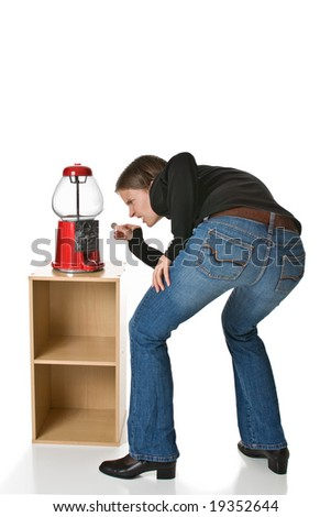 Confused or angry young woman in blue jeans tries to put a quarter into an empty gumball machine. - stock photo