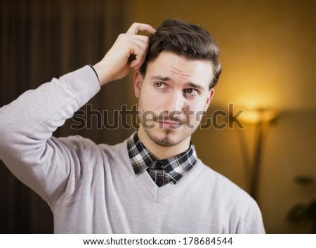 Confused or doubtful young man scratching his head and looking up. Indoors shot in a living room - stock photo