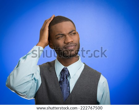 Confused. Portrait handsome business man thinking puzzled trying to remember something looking up isolated blue background. Human emotion facial expression feeling reaction body language perception - stock photo
