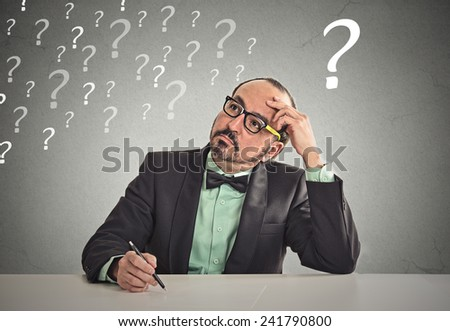 Confused puzzled business man sitting at table scratching his head thinking has many questions isolated office grey wall background. Human face expression emotion feeling body language perception - stock photo
