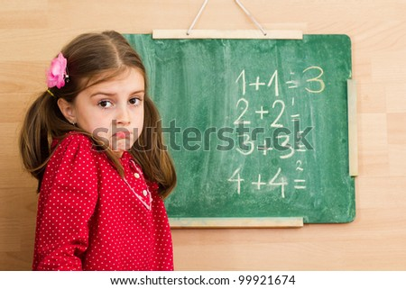 Confused schoolgirl standing in front of blackboard - problem with mathematics - stock photo