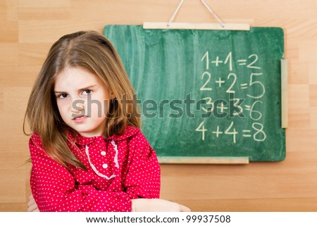 Confused schoolgirl standing in front of blackboard - problem with mathematics