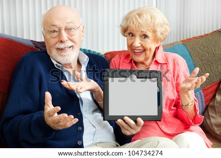 Confused senior couple holding their new tablet PC.  Blank computer screen ready for your text. - stock photo