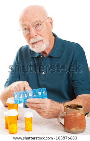 Confused senior man can't remember whether or not he took his pills.  Could be early sign of Alzheimer's Disease or dementia. - stock photo