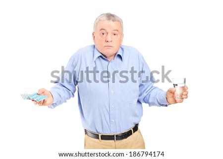 Confused senior man with pills and glass of water isolated on white background - stock photo