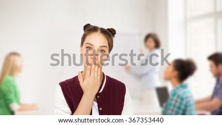 confused student girl covering her mouth by hand