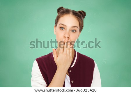 confused teenage student girl covering her mouth