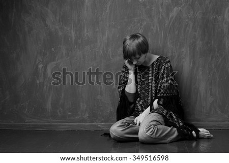 Confused woman is sitting against the wall. Black and white - stock photo