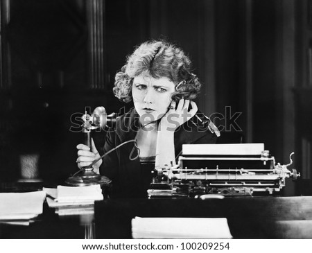 Confused woman on telephone - stock photo