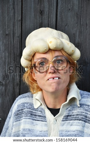 Confused woman with pumpkin on her head - stock photo