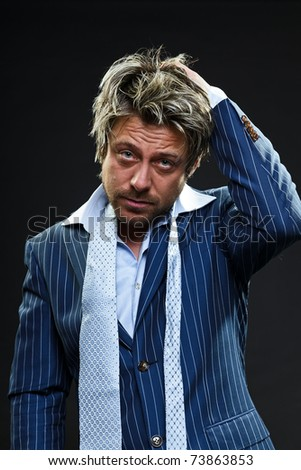Confused young business man in blue striped suit. Thinking. Lost. Crisis. Panic. Scared. Short blond hair. Studio portrait. Black background. - stock photo