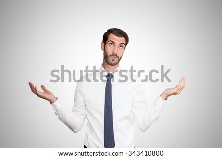 Confused young business man with hands at shoulder level. - stock photo