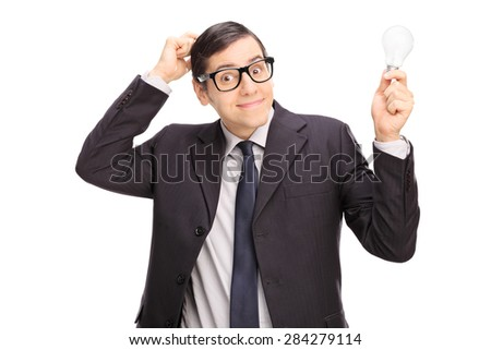 Confused young businessman in a black suit holding a light bulb and scratching his head isolated on white background