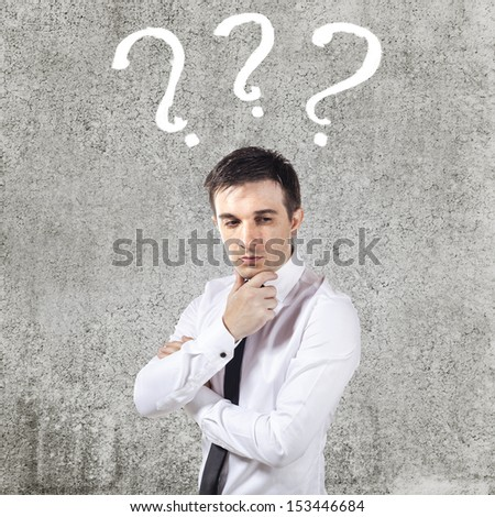 confused young businessman on grunge background