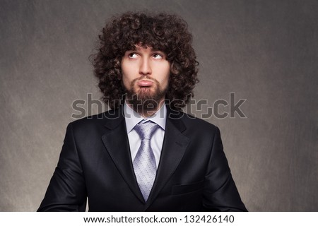 confused young businessman trying to make a decision - stock photo
