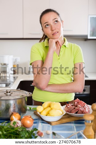 Confused young long-haired housewife thinking what to prepare for dinner