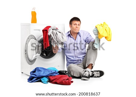 Confused young man doing laundry seated by a washing machine isolated on white background