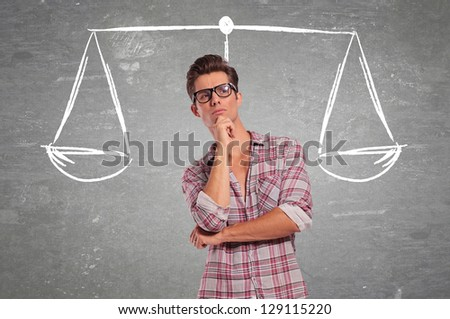 confused young man pondering all the choices before making a decision - stock photo