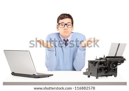 Confused young man with a laptop and typing machine on a table isolated on white background - stock photo