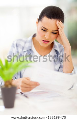 confused young woman doing home financial - stock photo