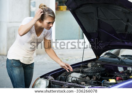 Confused young woman looking at broken down car engine on street - stock photo
