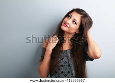 Confusion fashion brunette woman thinking and looking up on blue copy space background