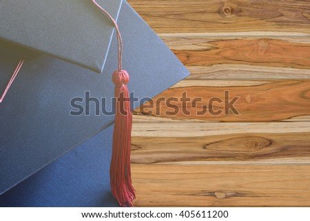 Congratulated the graduates in University,on wood background - stock photo