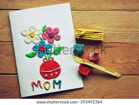 congratulation card mothers day, made from plasticine, on wooden table - stock photo
