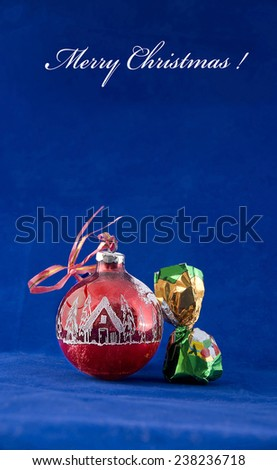 Congratulation merry Christmas. A Christmas ball and a chocolate in a wrapper with a congratulation on a blue background. - stock photo