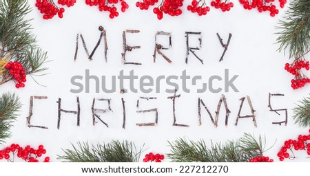 Congratulation text merry christmas written with broken wooden sticks on snow background inside berries fir branch frame rustic style - stock photo