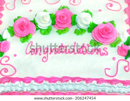 Congratulations in iced writing decorates frosted white cake.  Roses in pink and white sit in swirls amid green leaves.  Mounds of white frosting leaves room for personalization. - stock photo