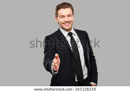 Congratulations! Portrait of cheerful young man in formalwear stretching out hand for shaking while standing against grey background - stock photo