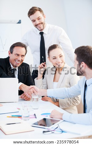 Congratulations! Two confident businessmen handshaking and smiling while sitting at the table together with their colleagues  - stock photo