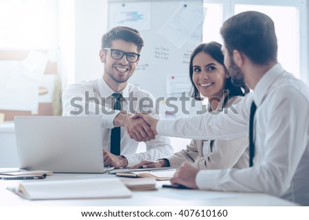 Congratulations! Two handsome man shaking hands with smile while sitting at the office table with their beautiful coworker - stock photo