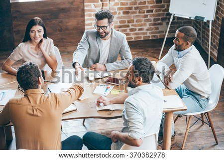 Congratulations with your promotion! Top view of two men shaking hands and smiling while their coworkers sitting at the table in office - stock photo