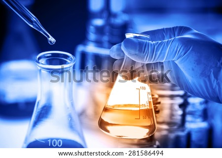 Conical flask in scientist hand with lab glassware background, Laboratory research concept  - stock photo