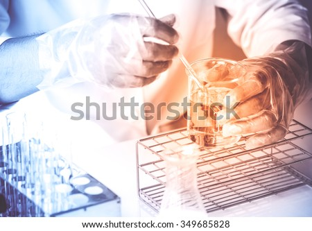 Conical flask in scientist hand with lab glassware background, Laboratory research concept;vintage process style - stock photo