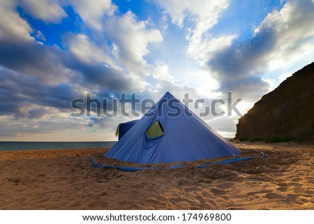 Conical tent on summer beach and blue sky with clouds.Wide angle view. - stock photo